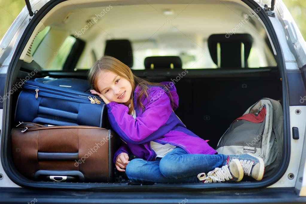 girl lying on suitcases in trunk of car