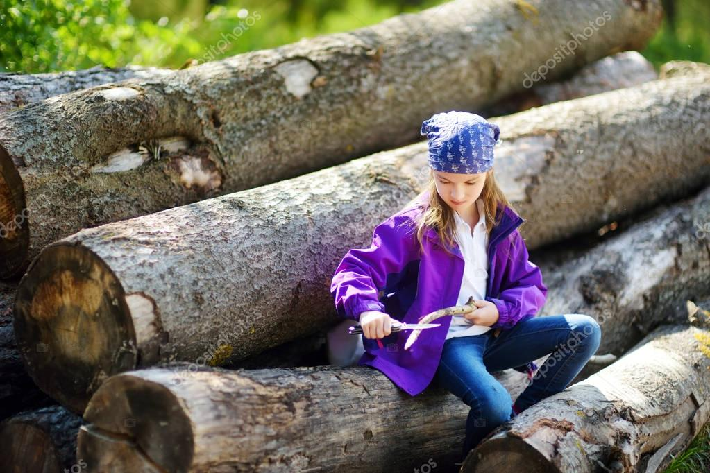 little girl sitting on tree logs
