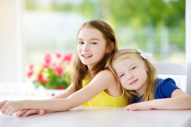 Two cute little sisters at home