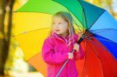 malá holčička drží duhový deštník