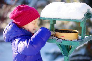 little girl feeding birds