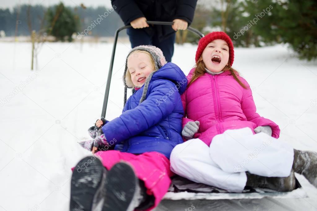little sisters on snow shovel