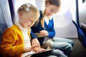 Entzückende kleine Mädchen, die im Flugzeug reisen