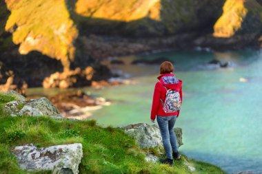 Tourist enjoying view of scenic rugged Cornish coastline near Port Isaac historic fishing village on sunny morning, Cornwall, England