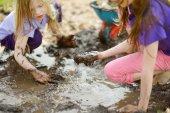 Fotografie Zwei lustige Mädchen spielen in einem großen nassen Schlamm Pfütze auf sonnigen Sommertag. Kinder immer schmutzig beim Ausheben im schlammigen Boden. Schmutzige Spiele im freien