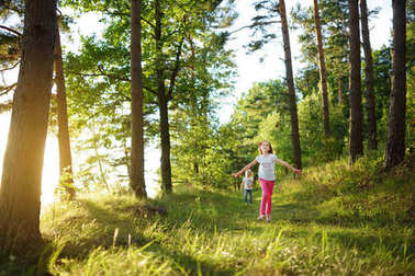 Two cute little sisters having fun during forest hike on beautiful summer day. Active family leisure with kids. Family fun.