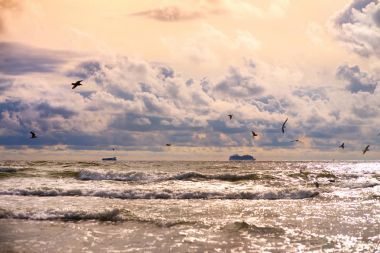 Dramatic sunset over the Baltic sea at summer. Purple clouds hovering over the waves on warm summer day.