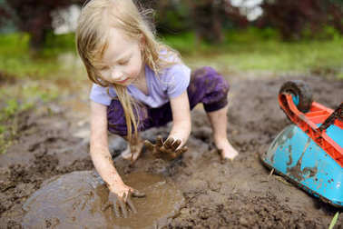 Funny little girl playing in a large wet mud puddle on sunny summer day. Child getting dirty while digging in muddy soil. Messy games outdoors.