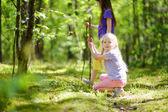 Dvě roztomilé sestřičky baví po lese na výlet na krásný letní den. Aktivní rodinnou dovolenou s dětmi. Rodinná zábava