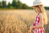 Fotografie Rozkošný dívka, která nosí slamákem chůze šťastně v pšeničné pole na teplé a slunečné letní večer. Roztomilé malé dítě v poli žito na západ slunce