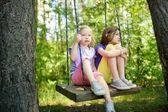 Dvě roztomilé sestřičky baví na houpačce spolu krásné letní zahrádce v teplého a slunečného dne venku. Letní outdoor volný čas pro děti.