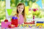 Adorabile ragazza avendo festa di compleanno a casa, saltando le candele sulla torta di compleanno. Bambini festa di compleanno con decorazioni colorate, regali e banner