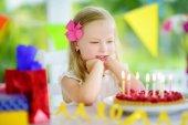 Rozkošný dívka s narozeninovou oslavu doma, foukání svíčky na narozeninový dort. Děti narozeninovou oslavu s barevné dekorace, dárky a nápisy