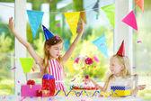 Fotografia Adorabile ragazza avendo festa di compleanno a casa, saltando le candele sulla torta di compleanno. Bambini festa di compleanno con decorazioni colorate, regali e banner