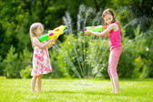 Photo Adorable little girls playing with water guns on hot summer day. Cute children having fun with water outdoors. Funny summer games for kids.