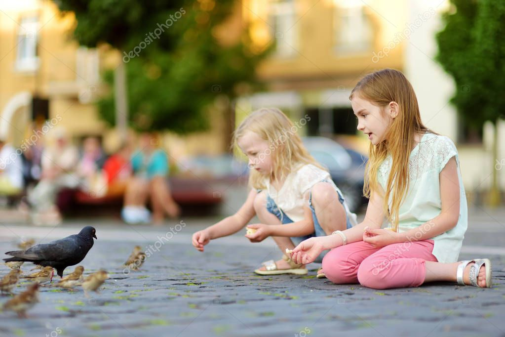 Two cute little sisters feeding birds on summer day. Children feeding pigeons and sparrows outdoors. Active leisure with kids.