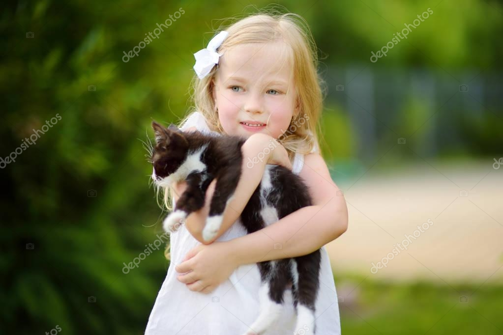 Cute little girl with her pet kitten on warm summer day. Kids and animals.