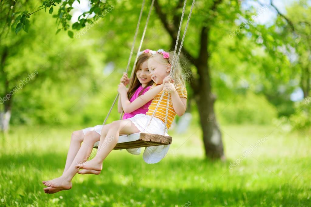 little sisters having fun on swing