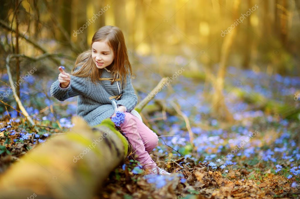 little girl picking flowers in forest