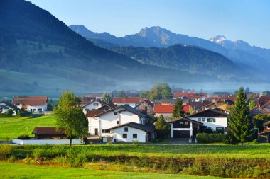 Breathtaking morning landscape of small Bavarian village covered in fog. Scenic view of Bavarian Alps at sunrise with majestic mountains in the background, Anger, Germany.
