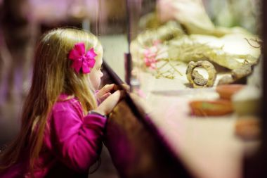 Cute little girl watching animals in the zoo. Child watching zoo animals through the window. Snakes in a terrarium.
