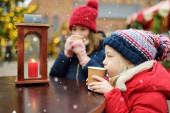 zwei entzückende Schwestern, die auf dem traditionellen Weihnachtsmarkt in Riga, Lettland, heiße Schokolade trinken. Kinder genießen Süßigkeiten, Bonbons und Lebkuchen auf dem Weihnachtsmarkt.