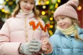 Fotografie zwei entzückende Schwestern mit hahnförmigen Lutschern auf dem traditionellen Weihnachtsmarkt in Riga, Lettland. Kinder genießen Süßigkeiten, Bonbons und Lebkuchen auf dem Weihnachtsmarkt.