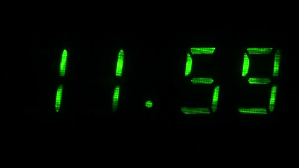 Digitális óra mutatja az időt a 11 óra 59 perc 12 óra 00 perc