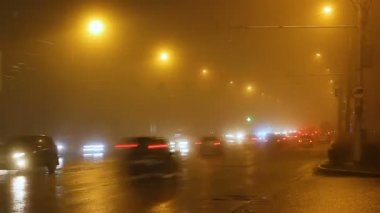 Street lights of city in fog and cars on way.