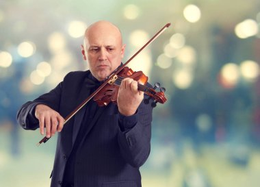 The violinist plays the violin on a background of holiday lights.