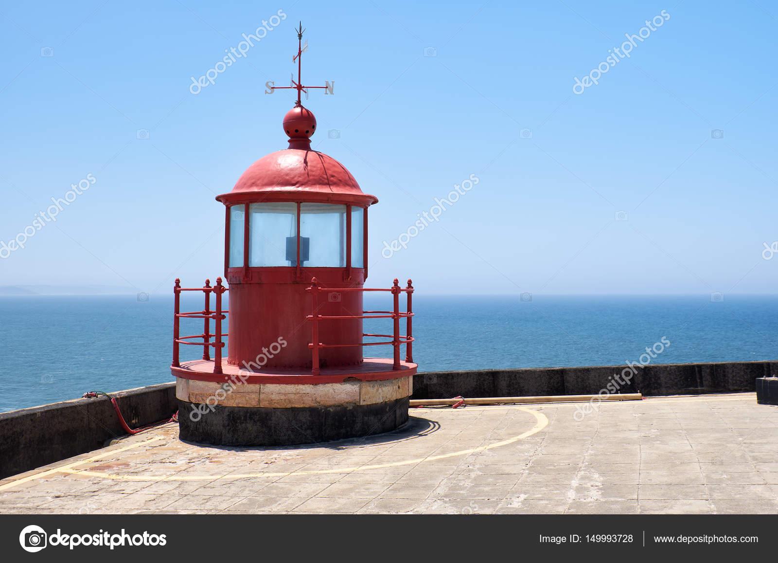 Rode vuurtoren lamp kamer op blauwe hemel en zee achtergrond in