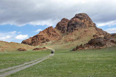 Mongolian natural landscapes with car on country road to the lak