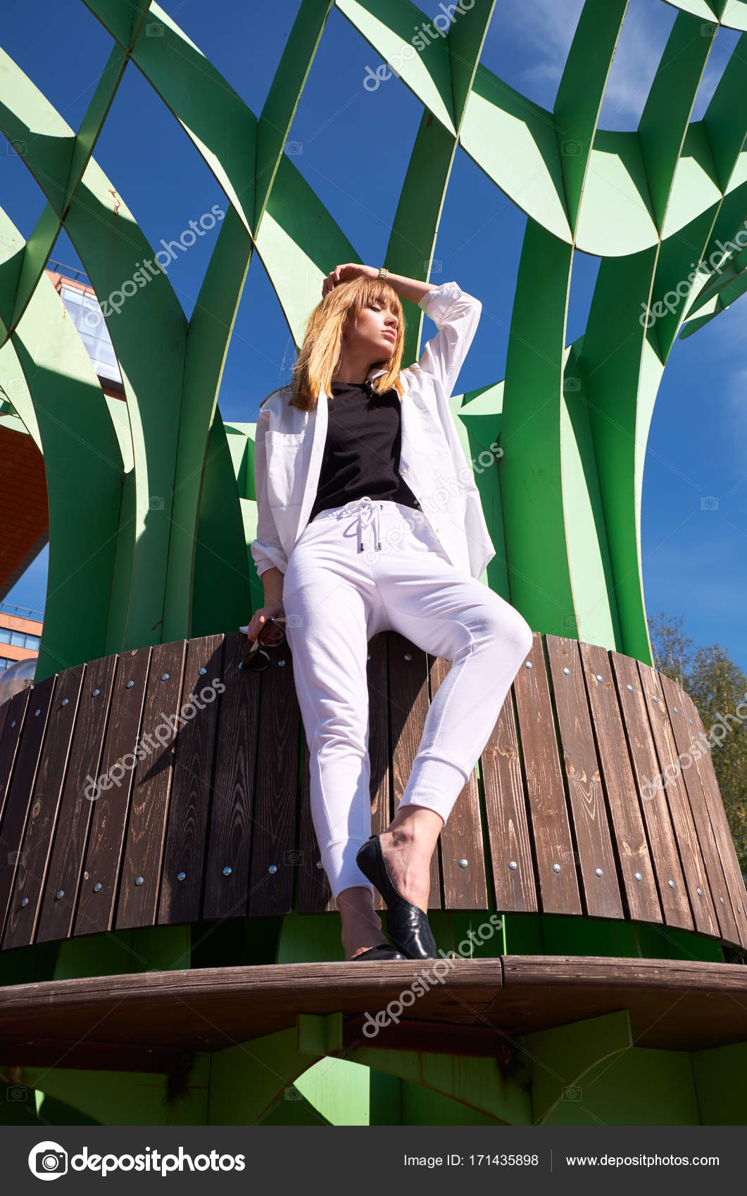 Modern young woman on the steps of building of information techn modern young woman in white clothes near building of information technology center in akademgorodok the symbol of novosibirsk technopark photo by biocorpaavc Images