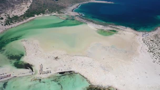 Letecký video pohled zezadu pohybující se drone na laguně Balos s písečnou mořskou pláží s opalováním a plavání turistů. Dimos Kissamou, prefektura Chania, Kréta, Řecko.