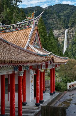 The colorful Chinese temple with the Nachi waterfalls on the bac