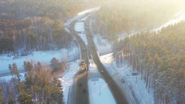 Letecký pohled shora dolů na zimní silnici v borovicovém lese pod sněhem. Auta a doprava na dálnici. Kamera se pohybuje po silnici. Sibiř, Rusko