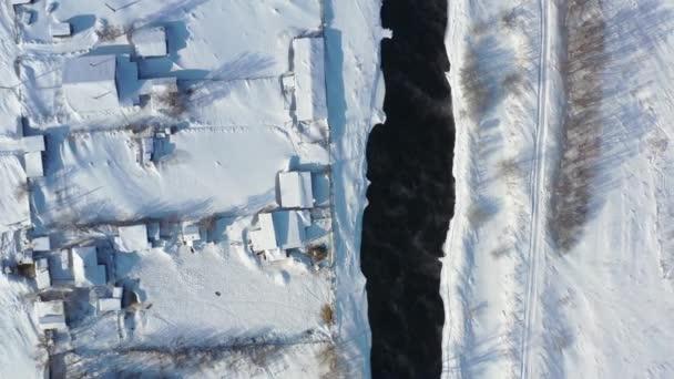 Légi felvétel a drón felemeléséről és forgatásáról az orosz Altai falun, Semiletkán télen. A kamera lefelé mutat. A Koksha folyó hóval borított partjai. Altai, Szibéria, Oroszország