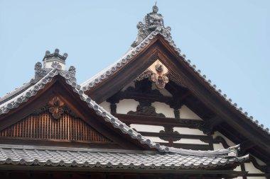 The curved roofs of Kuri, the temple kitchen, decorated with Morikuni (Onigawara  and kiri (family crest)) and gegyo (gable pendant). Kinkaku-ji temple. Kyoto. Japan