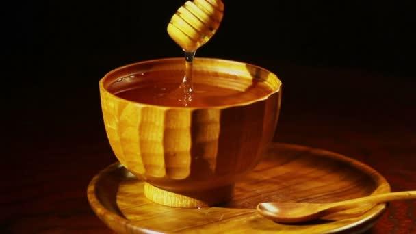med kapající z dřevěného držáku