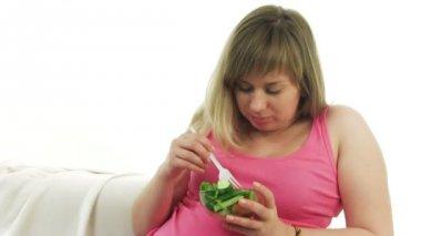 pregnant blonde woman eating salad