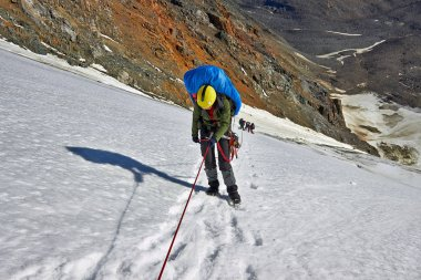alpinists hiking in snowy mountains