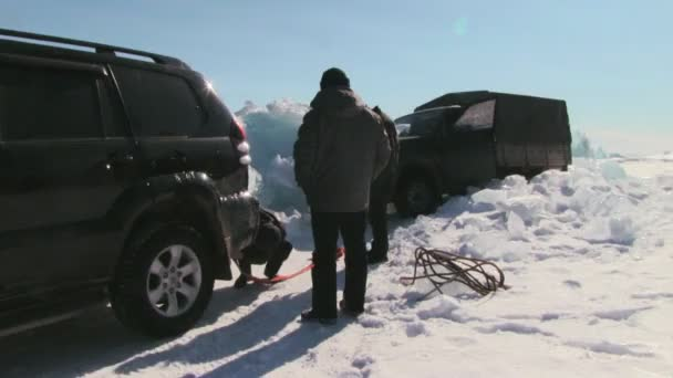 People by car stuck in snow