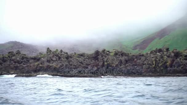zmrazené sopečná láva na pobřeží a na svazích hor v mlze, Kurilské ostrovy