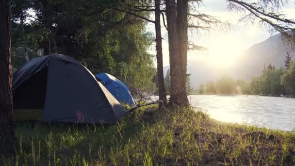 Dva stany v ranním lese na břehu horské řeky