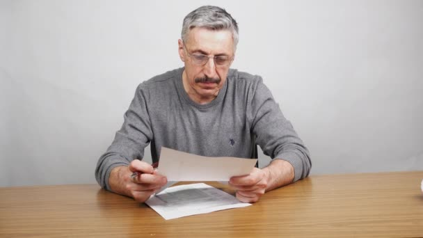 man filling out official forms on table