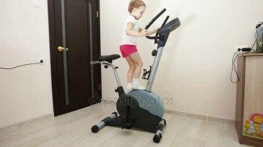 Young girl engaged on exercise bike in room