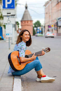 Fun smiling woman with a guitar sits on the curb