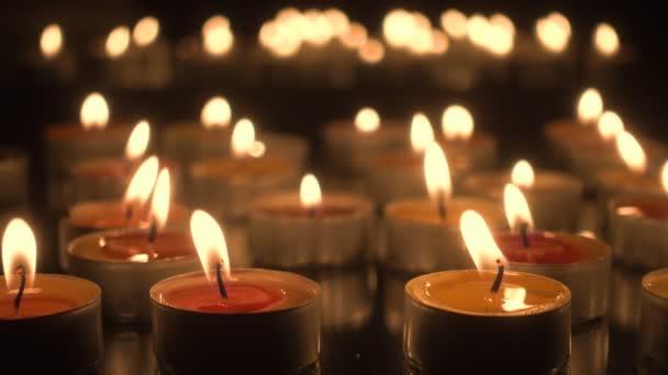 Hořící kostelní svíčky ve tmě