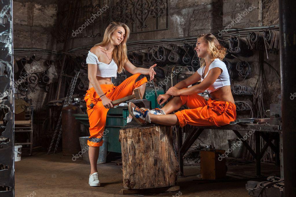 Sexig smed kvinnor i orange byxor talar på verkstad bakgrunden ...