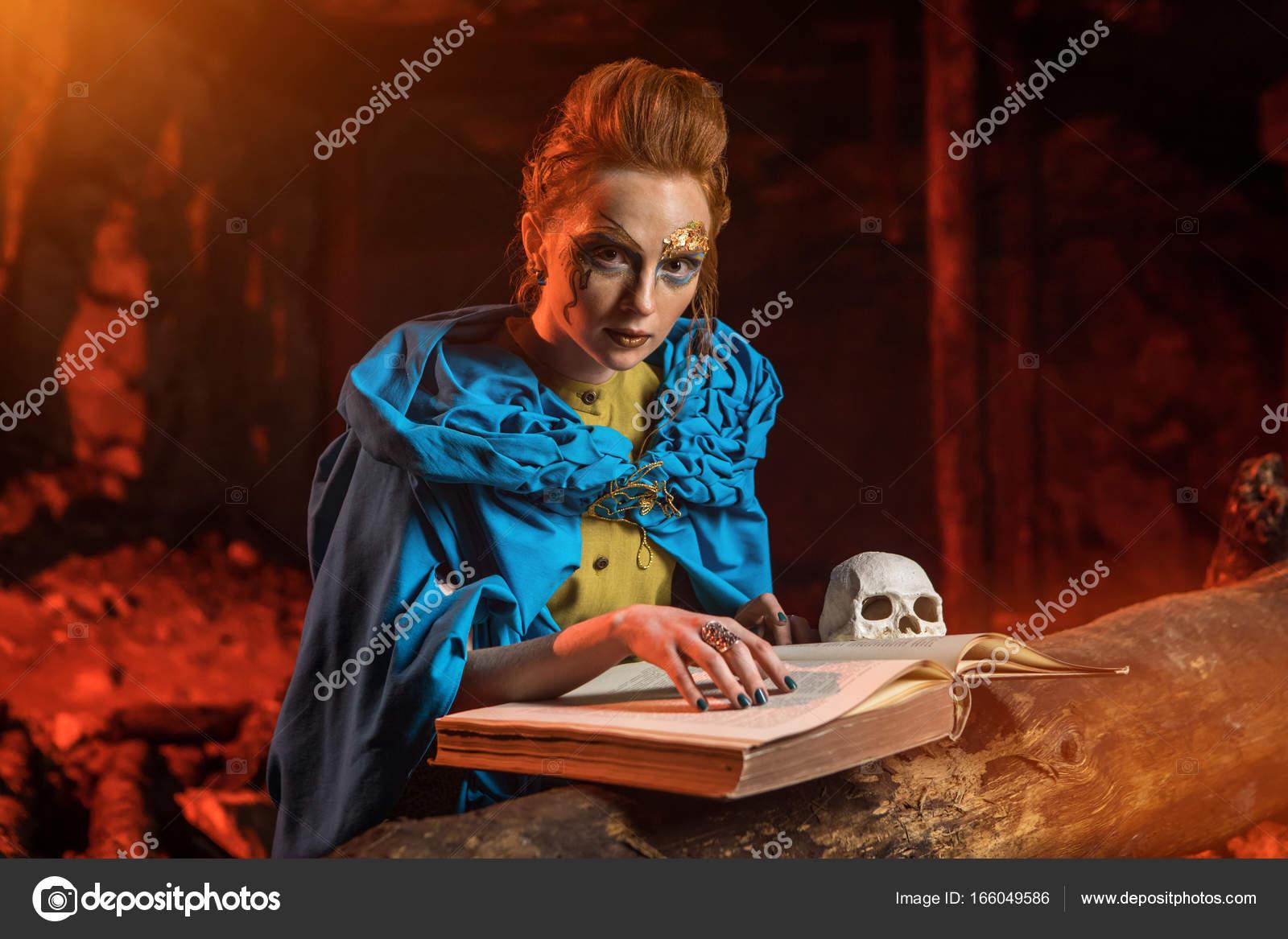 Hermosa bruja de pelo rojo con el libro de hechizos — fotos de stock